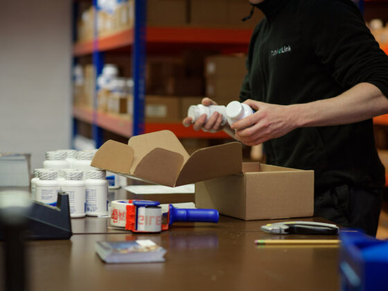 Person packing supplement products into a box